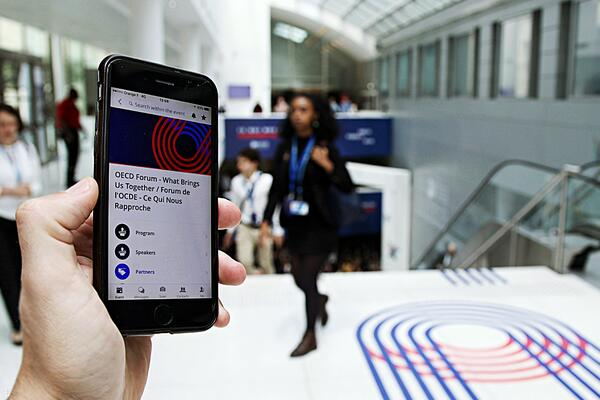 The OECD Forum used Swapcard's branded event app with a lot of blue (and some red) to engage delegates and attendees