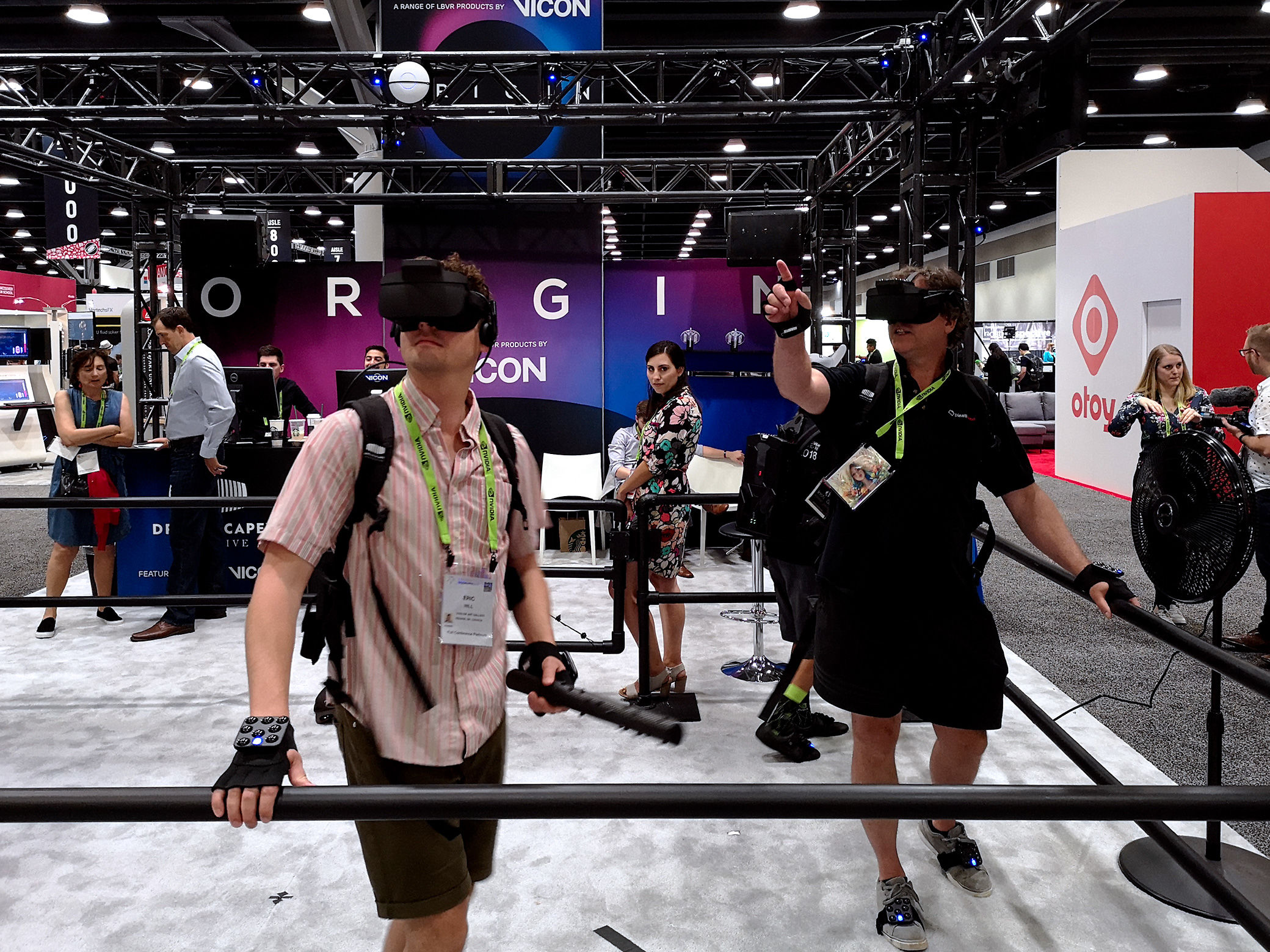Three participants testing out experiences based on Vicon's multi-player VR system you can walk around in